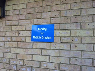 plaque for parking for mobility scooters on surgery exterior wall
